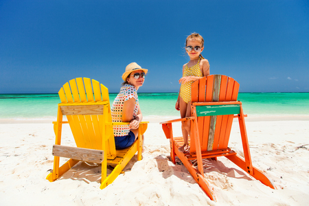 chairs: Mother and daughter family sitting on colorful wooden chairs at tropical beach enjoying summer vacation Stock Photo
