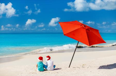 Kids in red Santa hats having fun at tropical beach during Christmas vacation Stock Photo