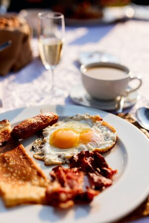 Delicious breakfast with fried eggs, bacon and vegetables Imagens