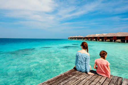 Mother and daughter sitting at wooden dock enjoying ocean view