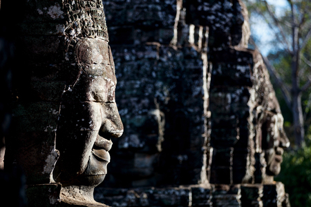 Faces of ancient Bayon temple popular tourist attraction in Angkor Thom, Siem Reap, Cambodia.