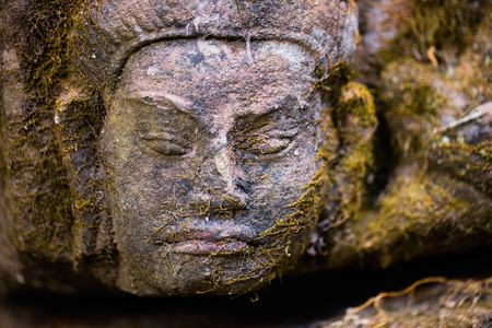 Mossy stone face in Angkor Archaeological area in Cambodia Stock fotó