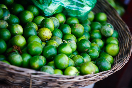 Assortment of fresh green limes on market tray