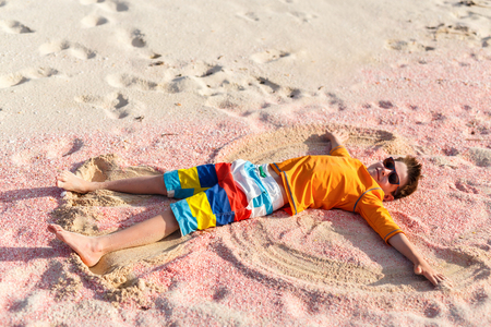 Boy making sand angel having fun on beautiful pink sand beach at tropical island of Barbuda in Caribbean
