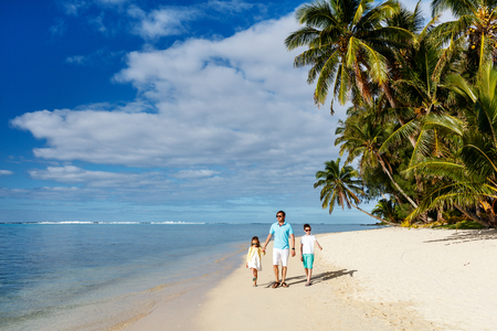 Back view of father and kids walking along tropical beach during summer vacation
