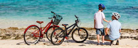 Father and kids enjoying sea view at tropical beach with their bikes parked nearby Фото со стока - 88497279