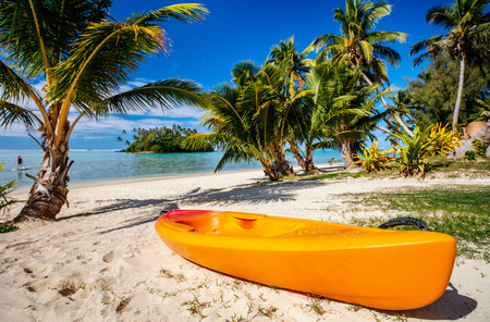 Colorful kayak at beautiful tropical beach with palm trees, white sand, turquoise ocean water and blue sky at Cook Islands, South Pacific