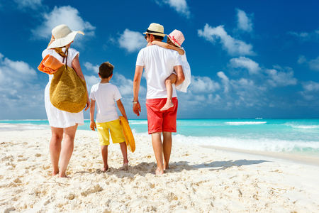 Back view of a happy family at tropical beach on summer vacation Standard-Bild
