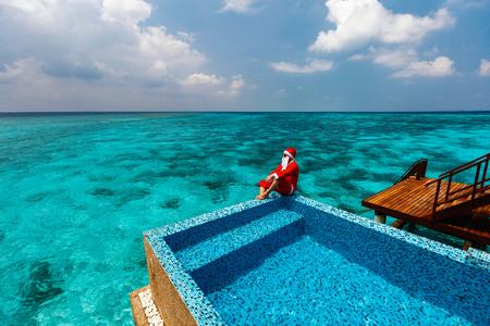 Christmas Santa Claus at tropical ocean luxury resort Stock Photo
