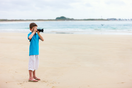 Young boy photographing at tropical white sand beach