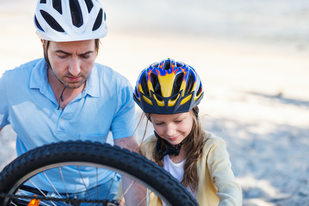 Little girl and her father repairing bicycle outdoors at summer
