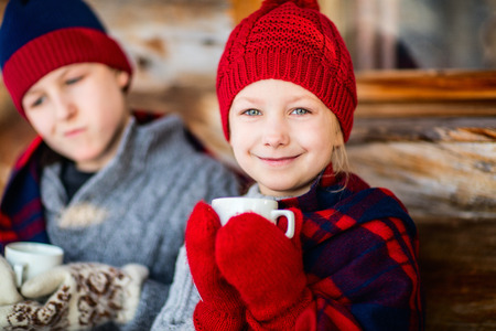 Kids outdoors on beautiful winter day drinking hot chocolate in front of log cabin vacation house Imagens