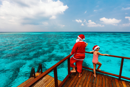 Christmas Santa Claus and little girl enjoying xmas travel vacation at tropical ocean