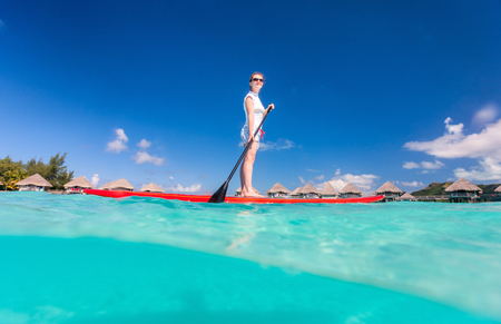 Active young woman on tropical beach vacation paddling on stand up board Foto de archivo