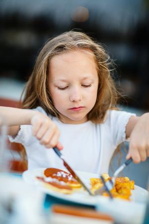 Adorable little girl eating pancake for a breakfast in restaurant Stock Photo