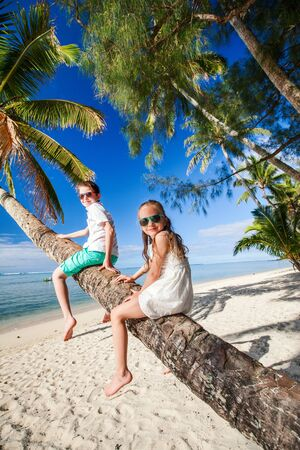 Kids at tropical beach sitting on palm tree during summer vacation Stock Photo