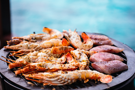 Close up of fresh lobsters and crayfish grilling on open fire 스톡 콘텐츠