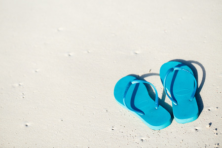 Turquoise flip flops on a tropical beach