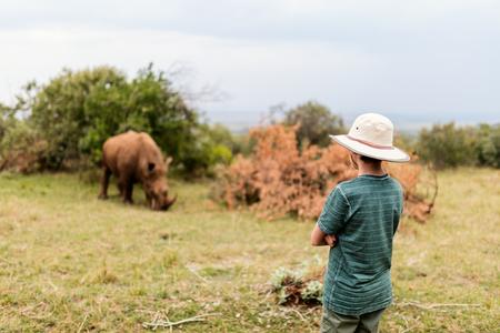 Back view of teenage boy on safari walking close to  white rhino Stock Photo