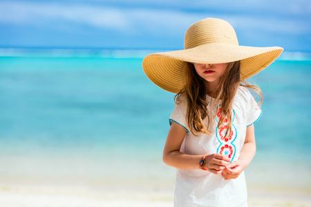 Очаровательны маленькая девочка на пляже во время летних каникул