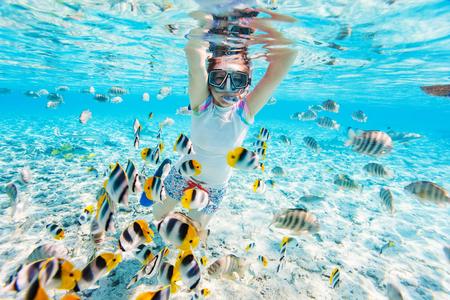 Vrouw snorkelen in duidelijke tropische wateren onder kleurrijke vis Stockfoto