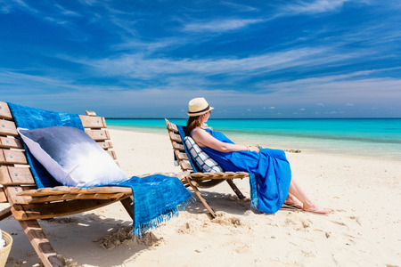 Back view of a young beautiful woman relaxing at white sand tropical beach