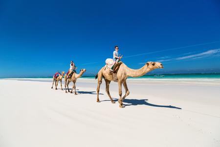 家族母と熱帯の白い砂のビーチでのラクダに乗る子供たち 写真素材 - 90337817