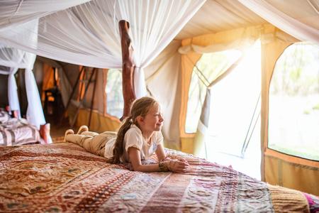 Little girl in safari tent enjoying vacation in Africa