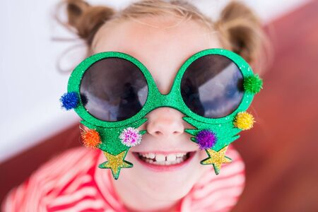 Adorable little girl in a funny Christmas glasses at tropical beach Stock Photo