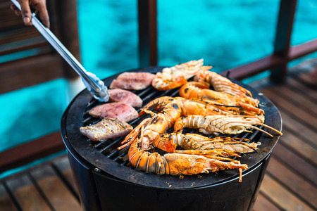 Close up of fresh lobsters and crayfish grilling on open fire Banco de Imagens