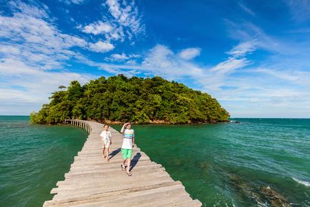 열 대 섬에서 인 도교를 걷고 여름 방학 동안 야외에서 아이 형제와 자매