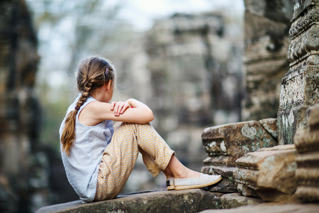 Little girl at ancient Preah Khan temple in Angkor Archaeological area in Cambodia Reklamní fotografie
