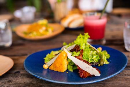 レストランでランチに提供されるベーコンの美味しい新鮮なシーザーサラダ 写真素材