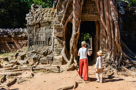 Family mother and child visiting ancient Ta Som temple in Angkor Archeological area in Cambodia