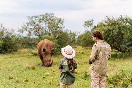 Achteraanzicht van familie op safari lopen dicht bij witte renoster