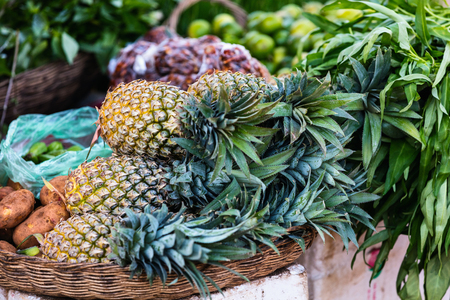 Assortment of fresh pineapples on market stall