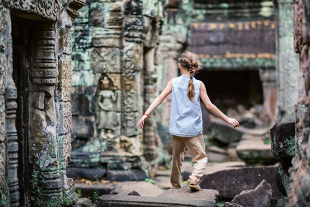Little girl in ancient Angkor Wat temple in Siem Reap, Cambodia Фото со стока