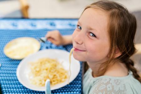 Portret van aanbiddelijk meisje die spaghetti voor een lunch eten bij restaurant