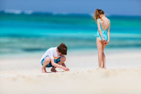 Kids having fun at tropical beach during tropical summer vacation playing together at beach