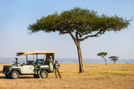 Family of father and kids on African safari vacation enjoying morning game drive