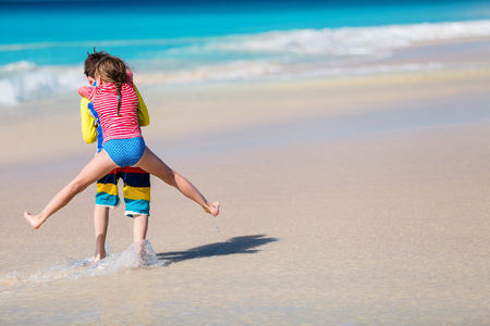 Kids having fun at tropical beach during Caribbean summer vacation playing together at shallow water