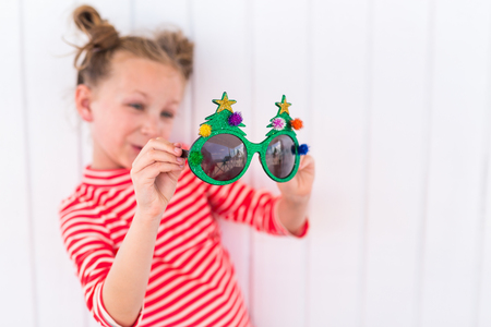 Adorable little girl in a funny Christmas glasses over white background Stock Photo