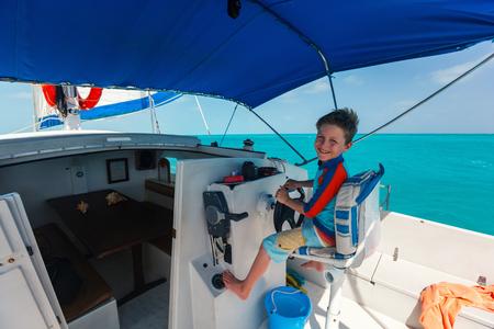 Schattige kleine jongen op zeilboot wiel Stockfoto - 91249603