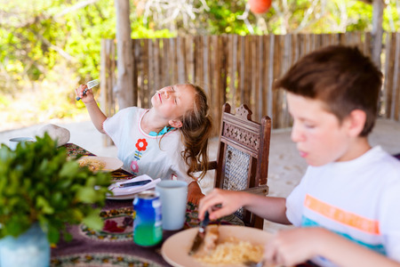 Kids eating spaghetti for a lunch at outdoor beach restaurant
