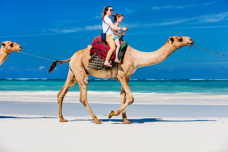 Family mother and daughter riding camels at  tropical white sand beach