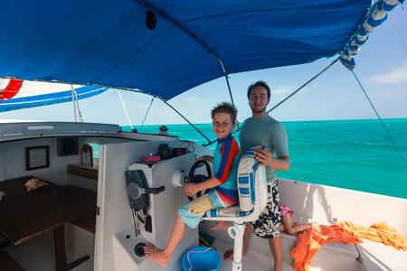 Schattige kleine jongen op zeilboot wiel Stockfoto - 91669807