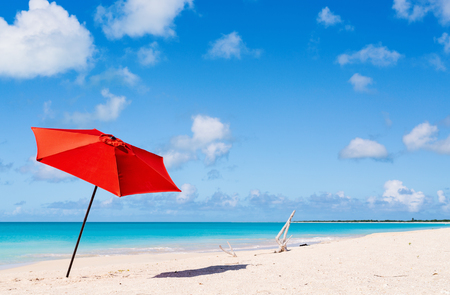 Idyllic tropical beach with red umbrella, white sand, turquoise ocean water and blue sky at deserted island in Caribbean Stock Photo