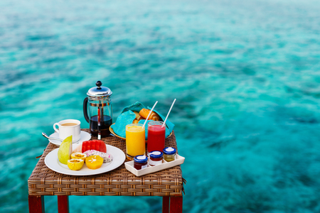 Delicious organic fruits, juice and coffee served for breakfast at tropical ocean edge in a luxury resort Stock Photo