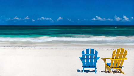 Colorful wooden chairs on beach at Caribbean coast