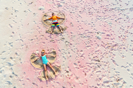 Above view of kids making sand angels on beautiful pink sand beach at tropical island of Barbuda in Caribbean